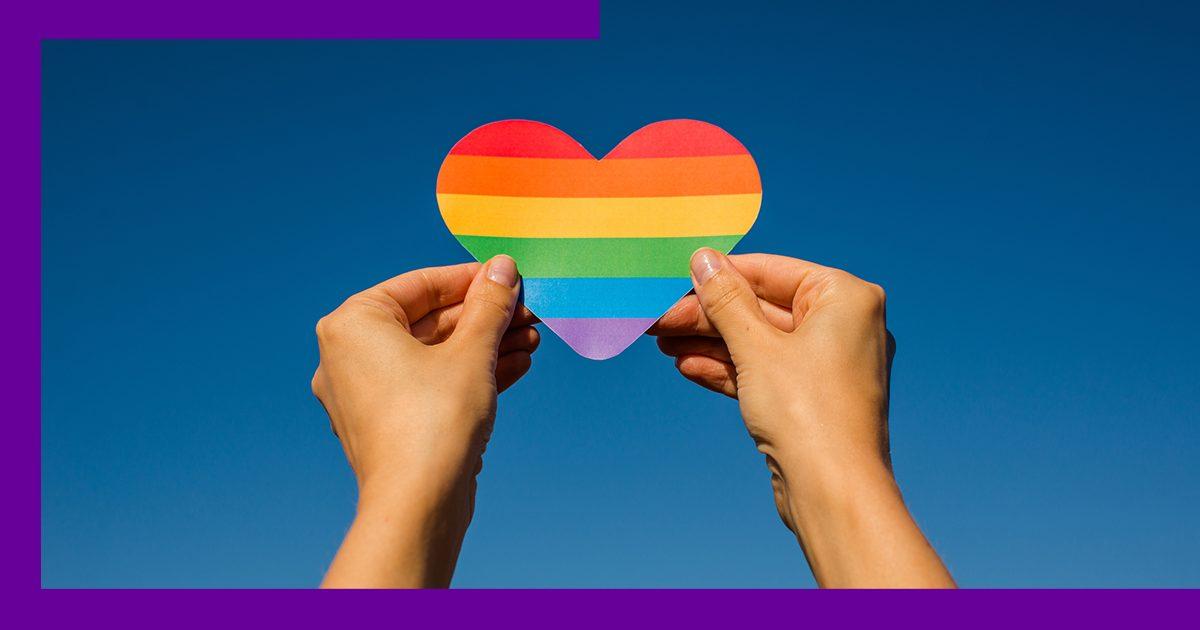Imagem de uma pessoa levantando um coração de papel com as cores de um arco-íris.