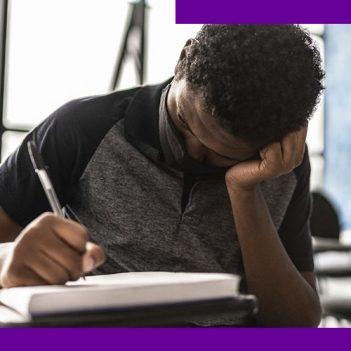 imagem de um jovem estudante na sala de aula, sentando em uma carteira escolar. Ele usa uma máscara de proteção individual e está com uma das mãos apoiada na cabeça, enquanto escreve em um caderno.