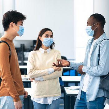 Imagem de três jovens, uma mulher e dois homens, usando máscaras, conversam de forma descontraída