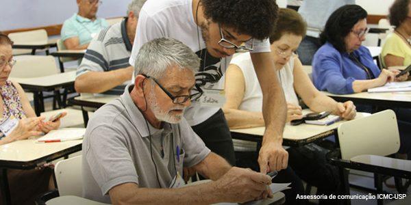 Aluno voluntário explica para uma pessoa idosa o funcionamento de um celular em sala de aula