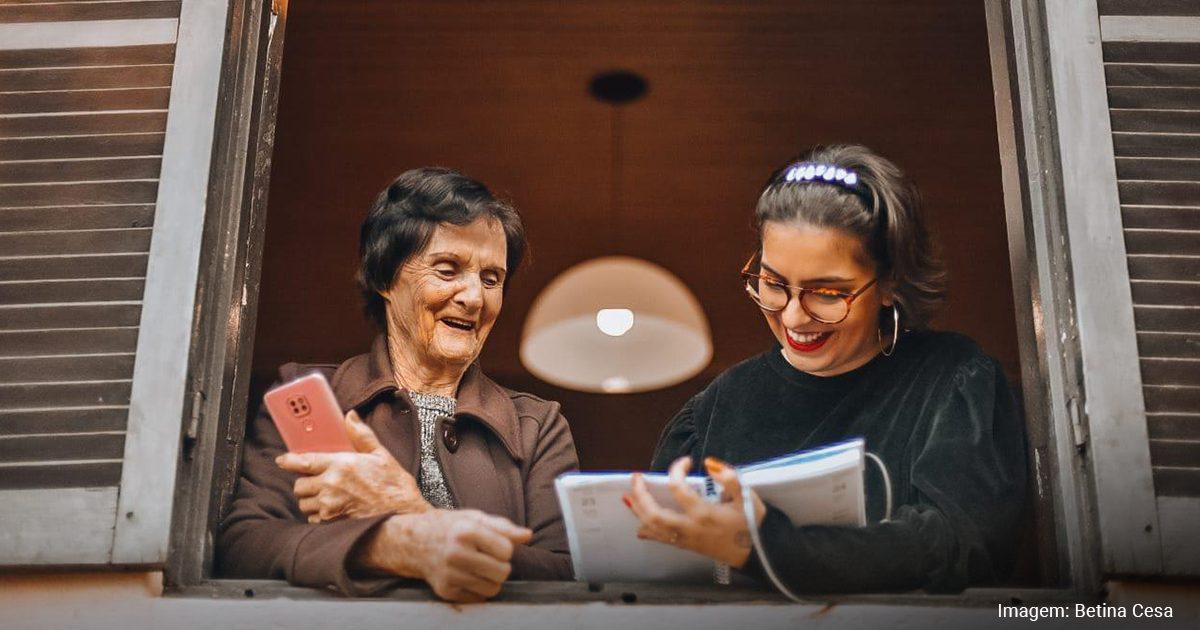 Imagem com Barbara Correa, que segura um caderno, e a sua avó Grete, com um celular nas mãos, na janela de casa