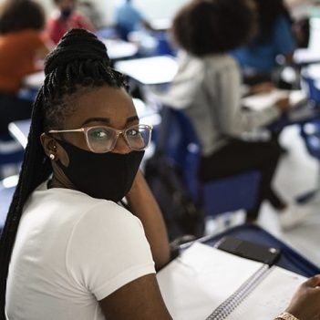 Imagem de uma estudante em sala de aula usando máscara