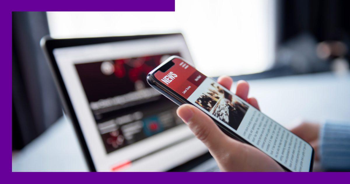 Imagem de uma pessoa segurando o celular ao lado de um computador com um site de notícias aberto