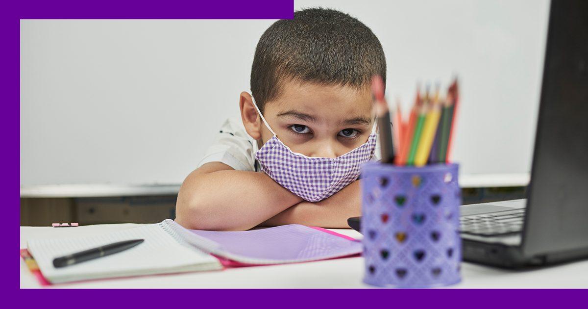 Imagem de garoto com rosto preocupado em ambiente escolar