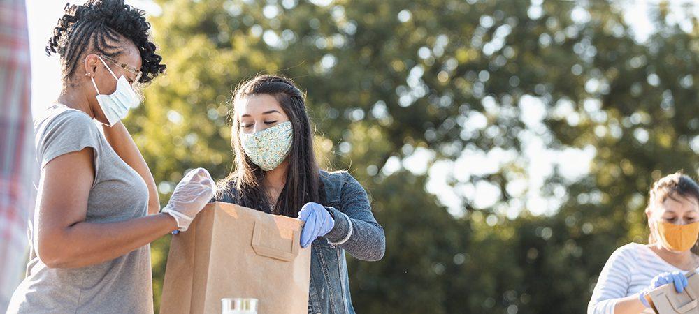 Imagem de três pessoas, voluntárias, distribuindo mantimentos