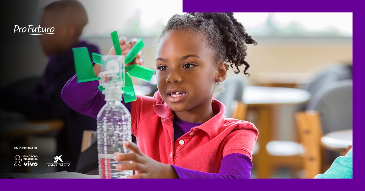Imagem de uma menina em primeiro plano, em sala de aula, brincando com material reciclado