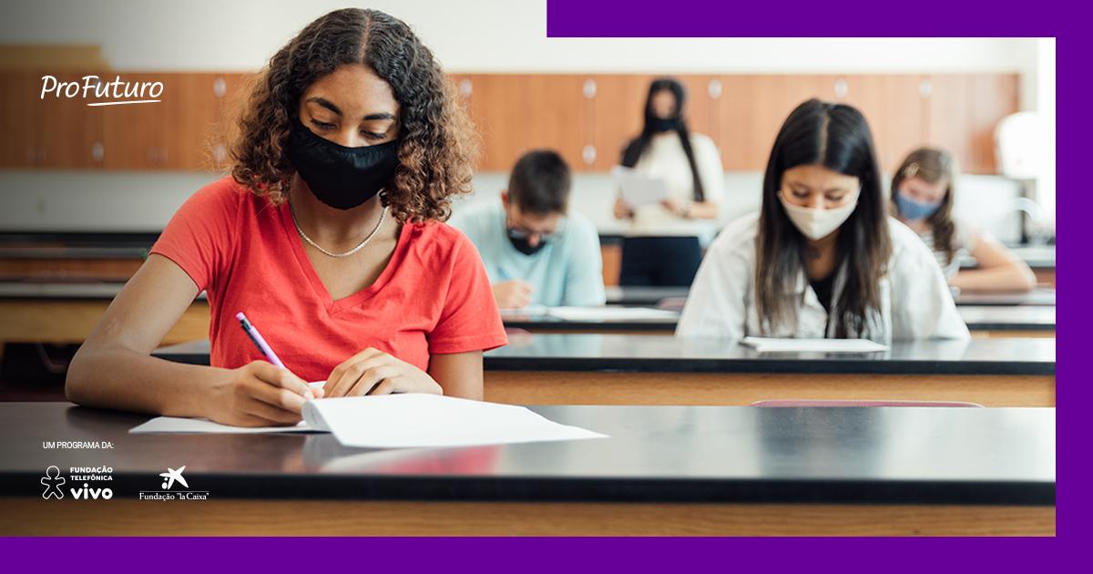 Imagem de estudantes fazendo prova em sala, com máscaras e distanciamento social
