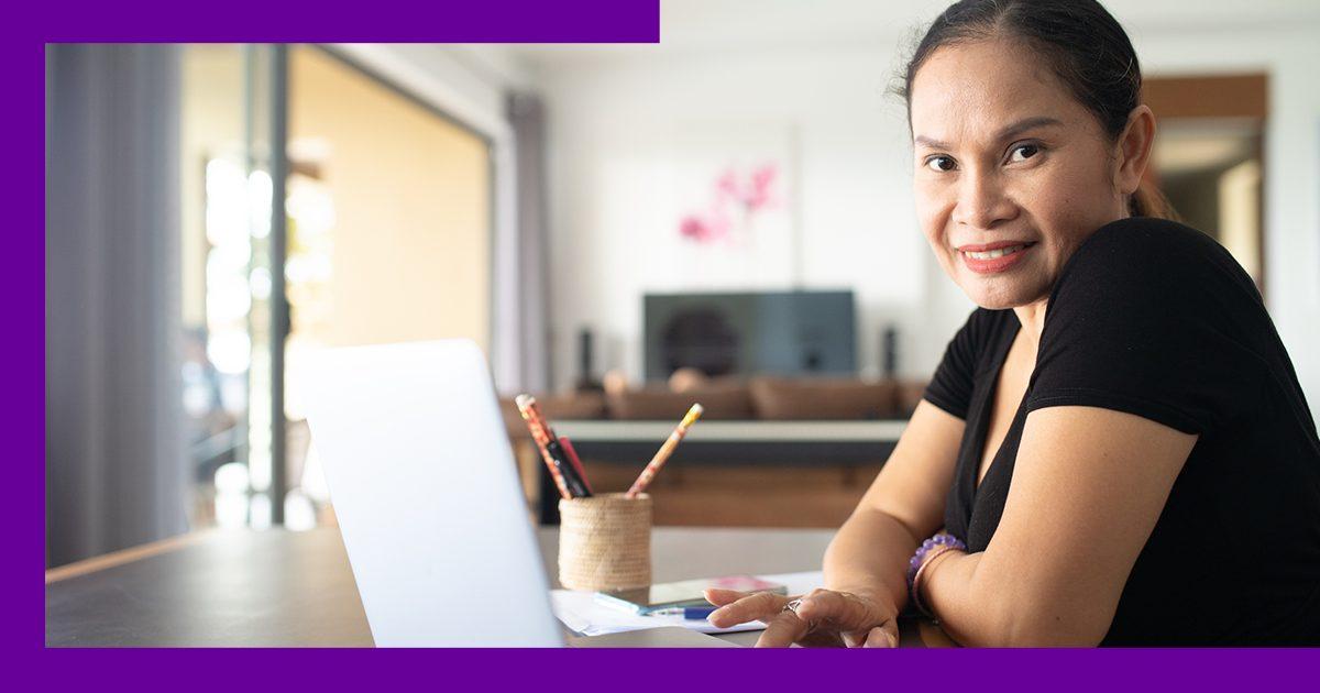 Imagem de uma mulher olhando para a câmera ao lado de um notebook na mesa
