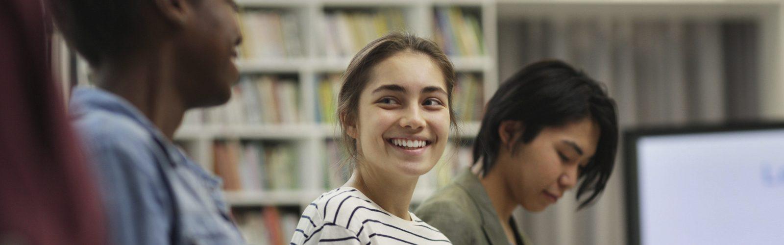 Imagem genérica de uma garota ao lado de outros jovens
