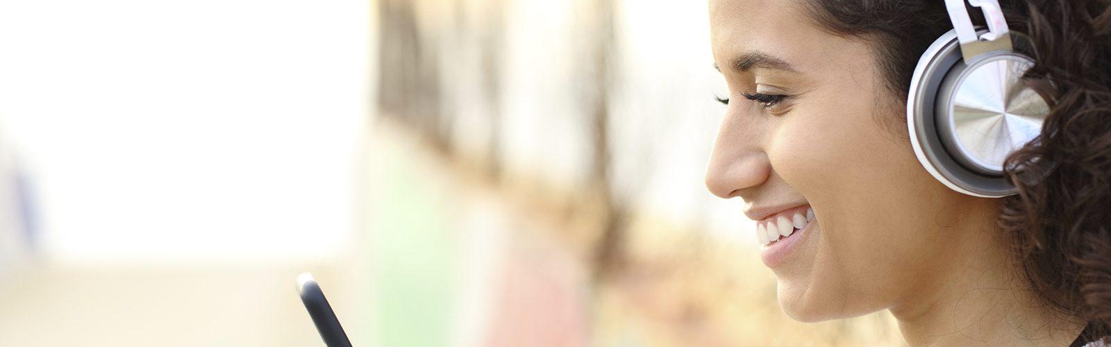 Imagem genérica de uma garota com fones de ouvido e olhando tablet