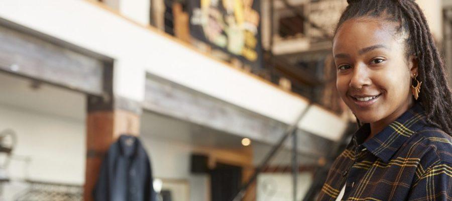Imagem de uma mulher dentro de uma loja com um tablete nas mãos