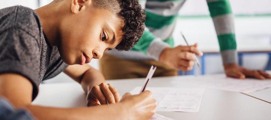 Imagem de um aluno escrevendo em sala de aula