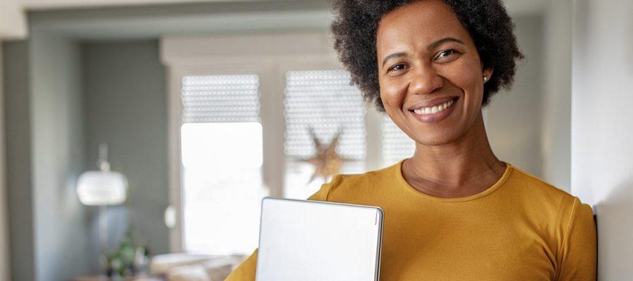 Imagem de uma mulher em uma sala de estar com livros e computador nos braços