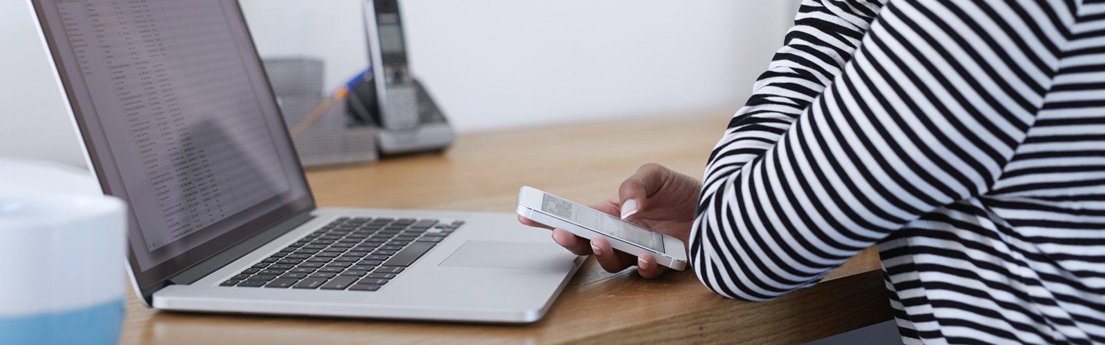 Imagem de uma mulher segurando um celular em frente ao computador
