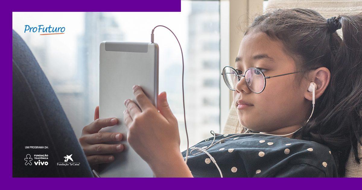 Imagem de menina vendo um tablete com fones de ouvido, deitada