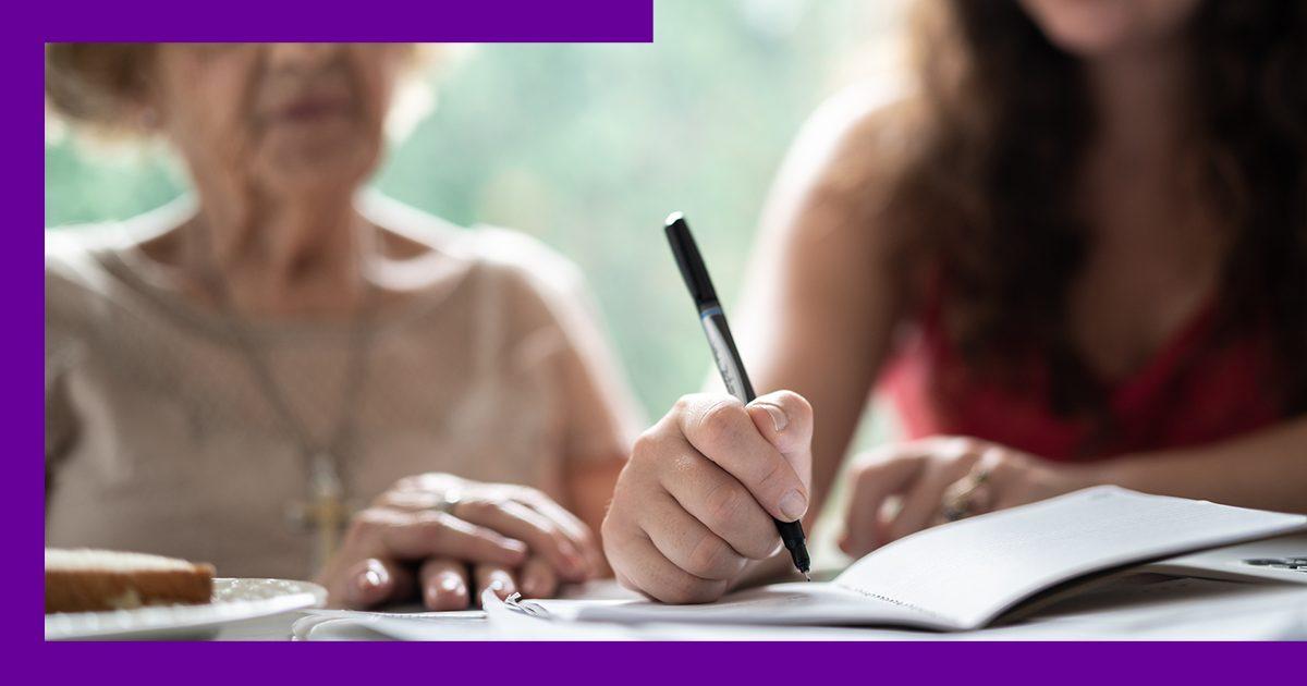 imagem de duas mulheres lado a lado, uma senhora e uma jovem, com destaque para as mãoes da jovem escrevendo em um caderno.