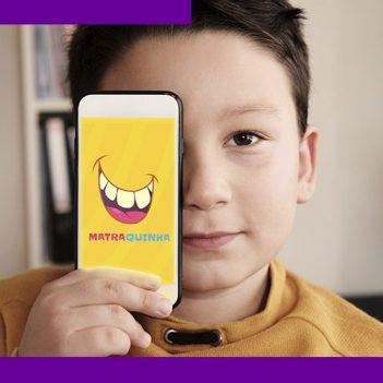 imagem mostra uma criança com um celular na mão, onde se vê o nome do aplicativo Matraquinha