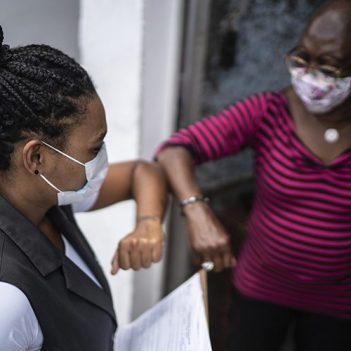 Imagem mostra duas mulheres de máscaras de proteção tocando os cotovelos para se cumprimentar durante a pandemia