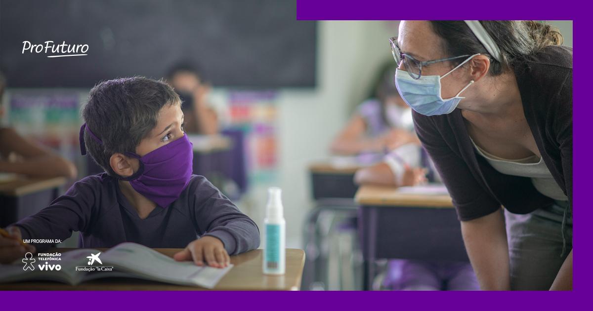 Imagem de uma educadora conversando com um aluno, os dois de máscara