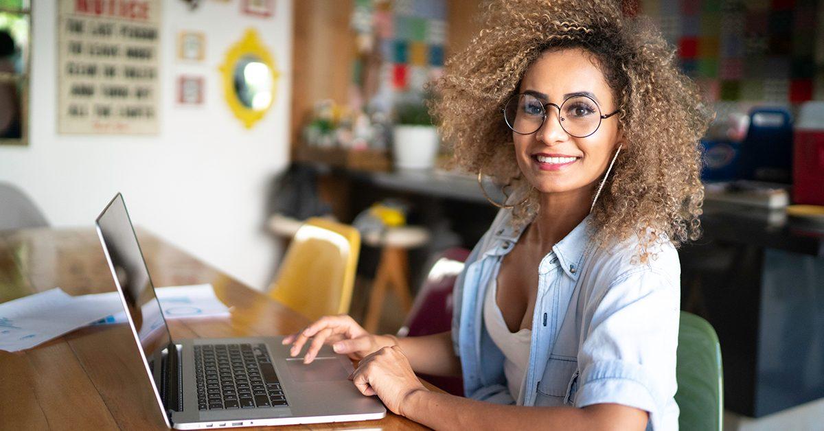 imagem de uma mulher sorrindo em uma sala residencial sentada em frente a um computador