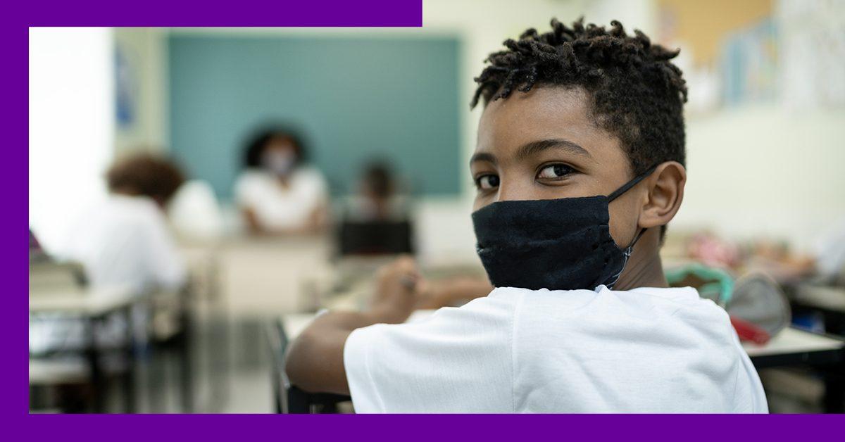 imagem de um estudante na sala de aula usando máscara de proteção facial