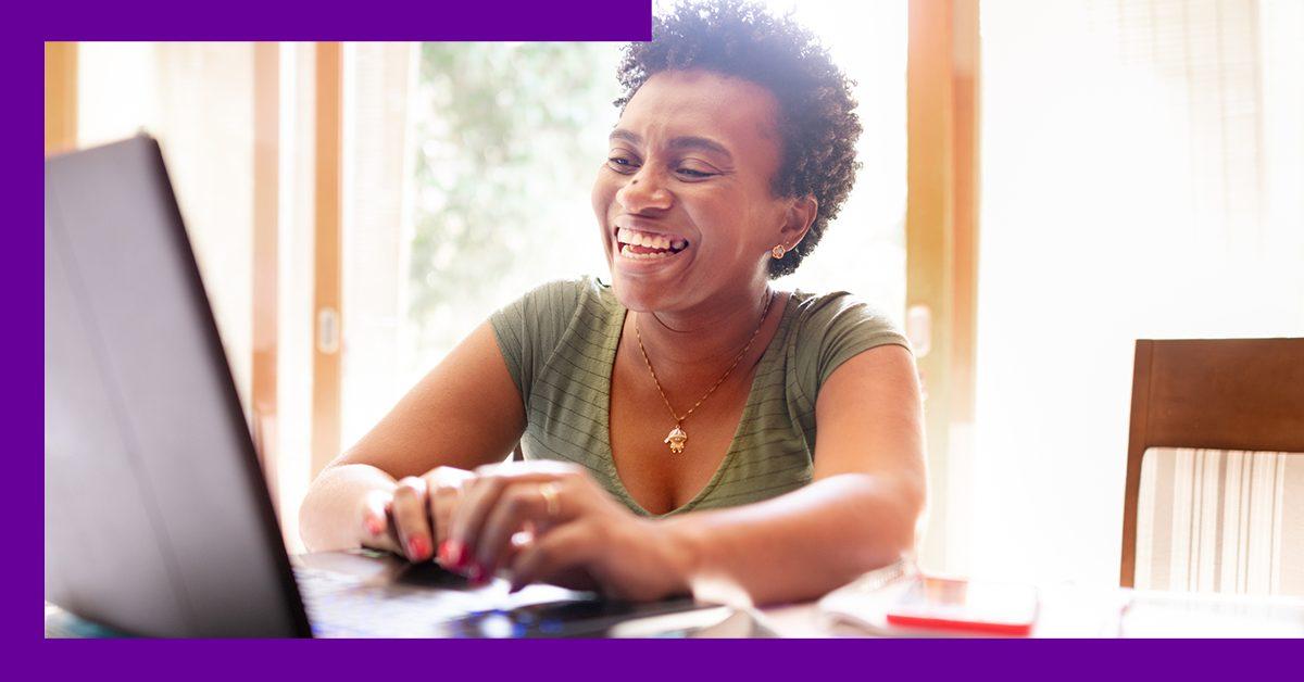 Imagem mostra professora negra sorrindo e digitando em um notebook