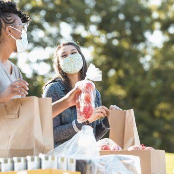 Imagem mostra duas moças felizes, uma delas é negra, a outra é branca. Ambas estão usando máscaras e manuseando sacolas.