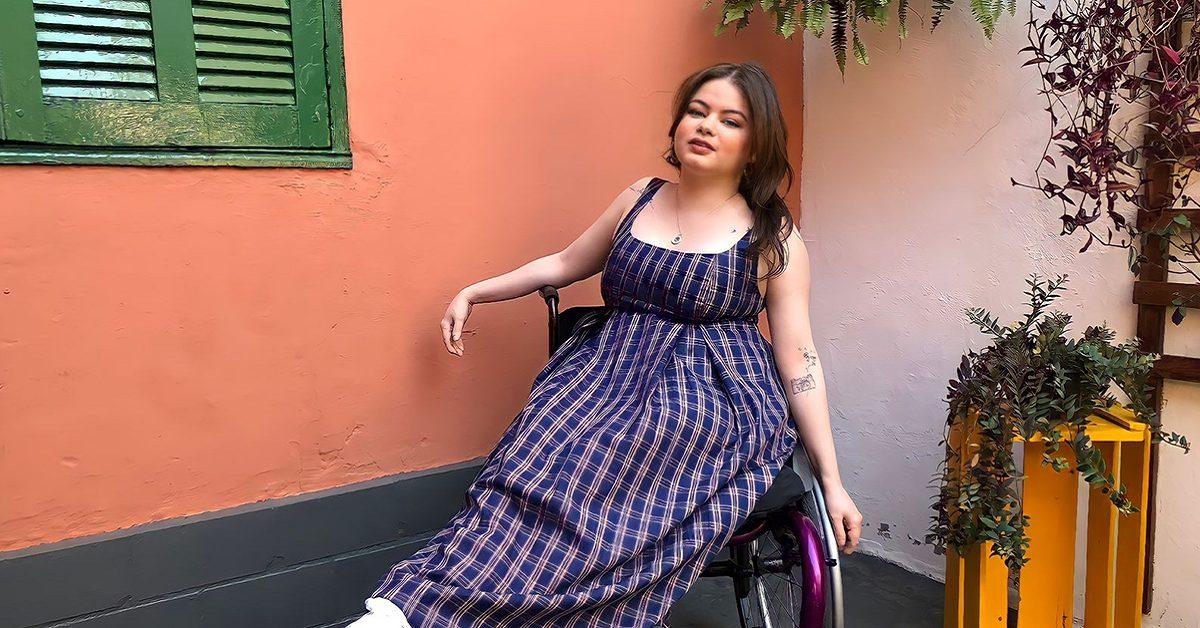 Imagem mostra a jovem fotógrafa e modelo usando um vestido xadrez, sentada em uma cadeira de rodas em um local com plantas