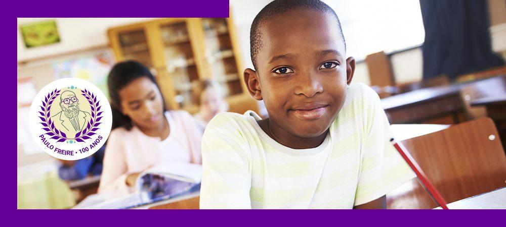 Imagem mostra garoto em sala de aula, sorrindo e segurando um lápis com a mão direita. A imagem contém selo comemorativo do centenário de Paulo Freire