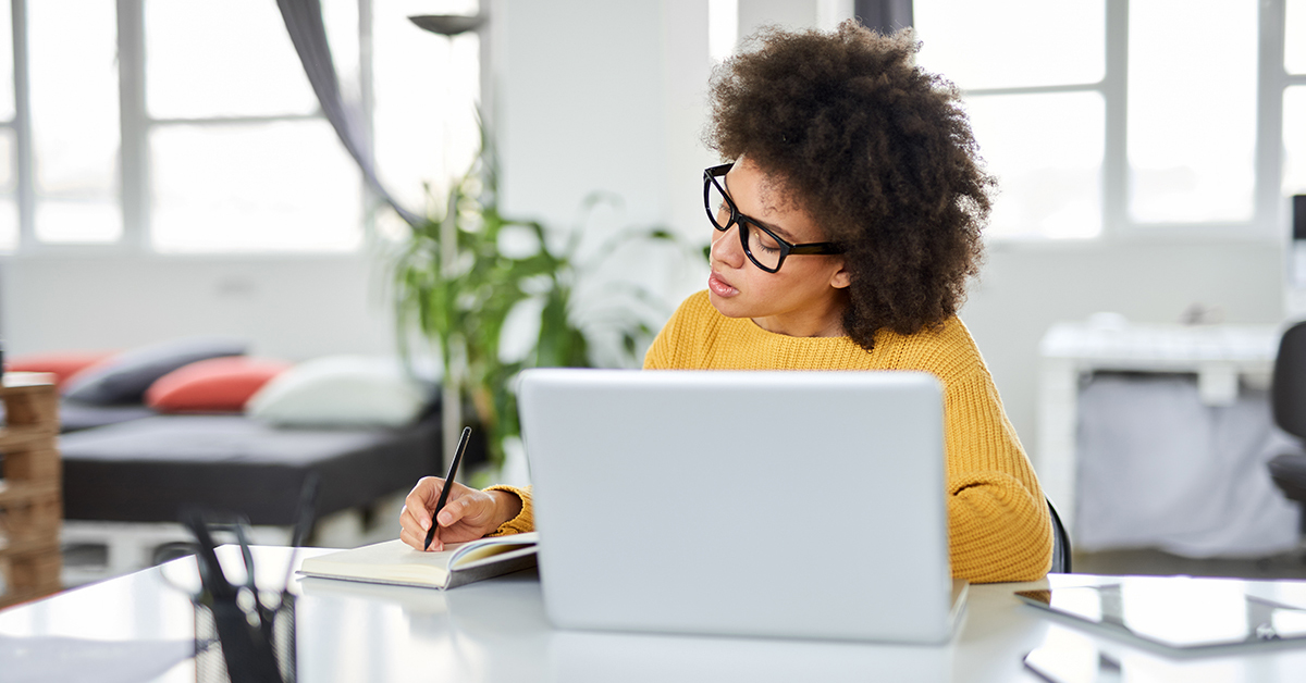 Imagem mostra mulher de óculos estudando em frente a um notebook e usando um caderno e caneta