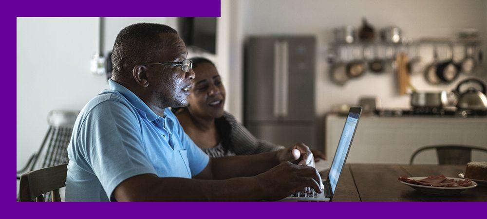 Imagem mostra um homem e uma mulher negros utilizando um computador. Eles estão em casa. O homem veste uma camisa azul. A mulher usa uma blusa cinza e tem cabelos compridos.
