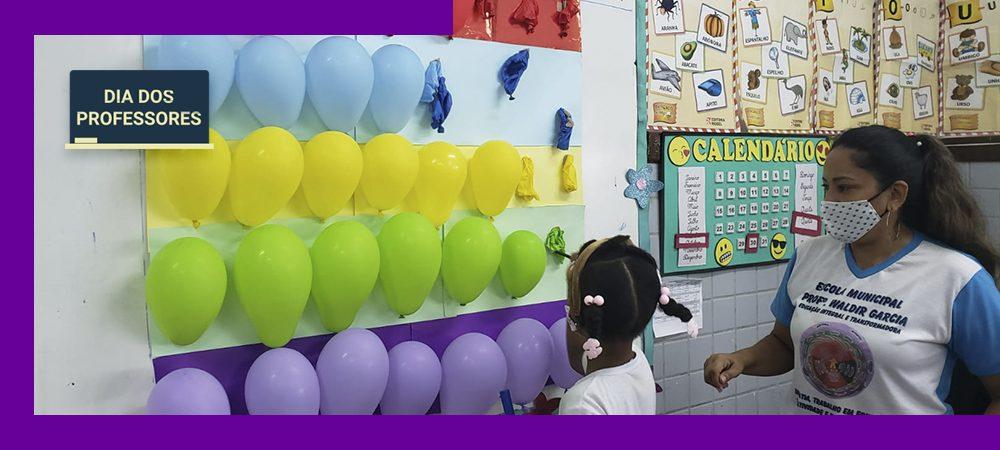 Imagem mostra professora com uma aluna em frente a um painel de balões coloridos. A menina está estourando um dos balões