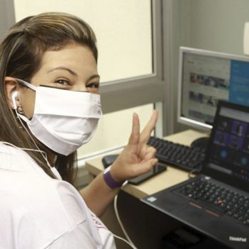Imagem mostra voluntária. Ela usa máscara, está sorrindo e sentada em frente a um notebook assistindo a uma live do Dia dos Voluntários