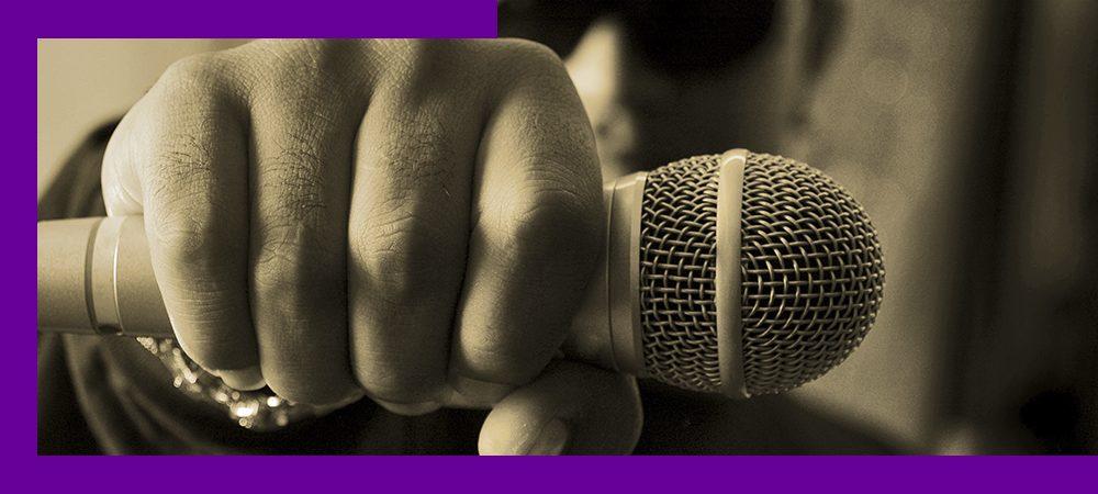 Imagem mostra um jovem segurando um microfone. A imagem está bem próxima do microfone e da mão do jovem.