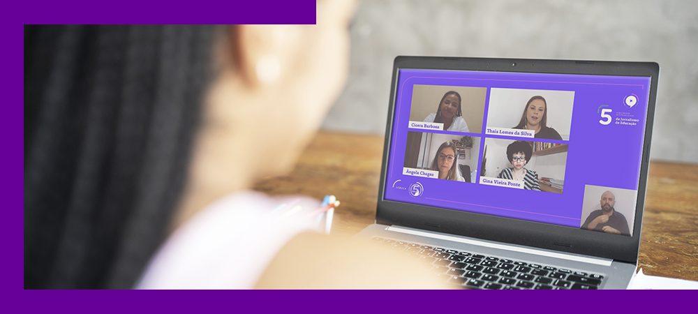 Imagem mostra uma garota de costas, assistindo ao evento da Jeduca em um notebook.